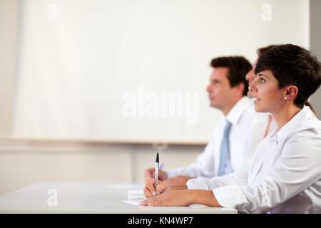 Portrait d'un joli portrait à la direction lors de la présentation en face d'un collègue sur fond de bureau - copyspace. Banque D'Images