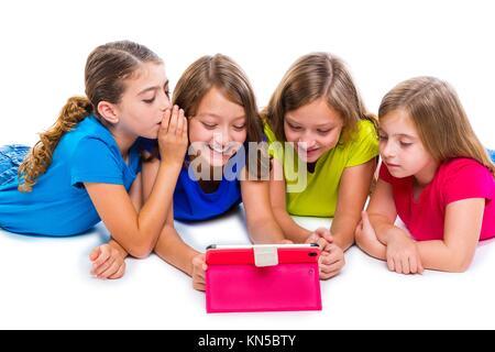 Sœurs cousins kid filles avec tech tablette pc jouer heureux couché sur fond blanc. Banque D'Images