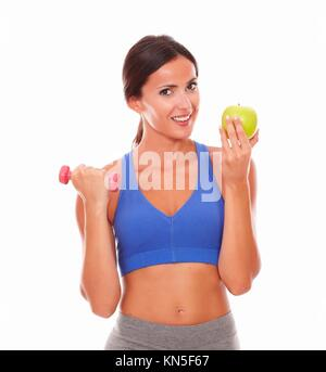 Slim young woman holding apple et l'haltère en regardant vous sur fond isolé. Banque D'Images