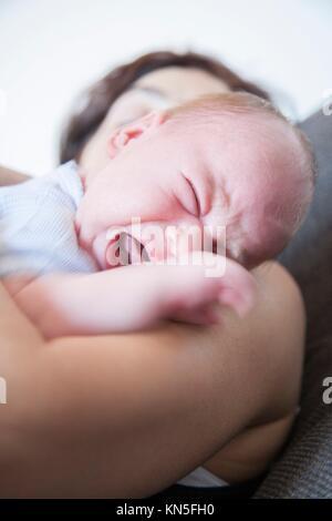 L'âge d'un mois bébé pleurer et crier crier fermez les yeux langue sur brunette woman mère épaule. Banque D'Images