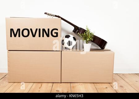 Les boîtes de déménagement, guitare, fleur et footall. Banque D'Images