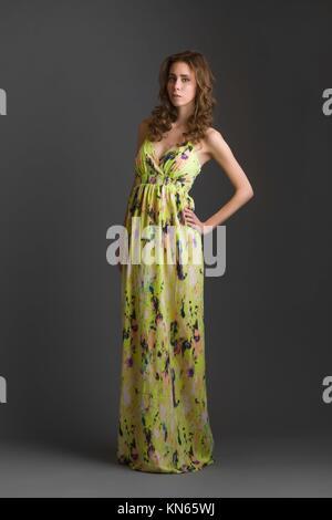 Belle fille portant robe jaune, fond gris. Banque D'Images