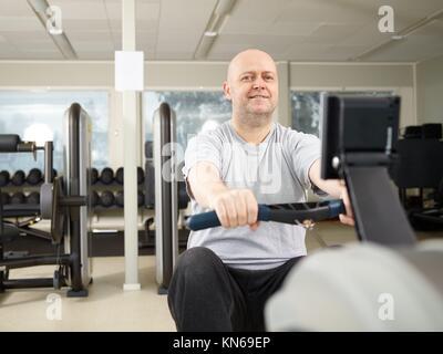 Homme mature prend soin de sa santé et il l'aviron dans le sport. Banque D'Images