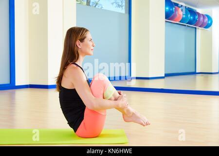 Femme Pilates rouler comme une boule d'entraînement à l'exercice de sport indoor. Banque D'Images