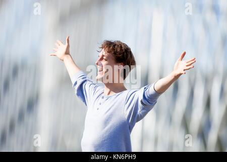 Heureux Jeune homme en tendant son bras dans l'émotion à l'extérieur. Banque D'Images