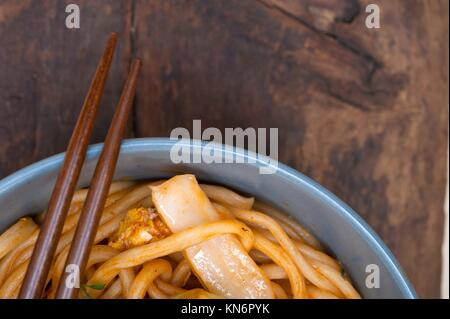 Tiré à main chinois nouilles ramen étirée sur un bol avec des baguettes. Banque D'Images