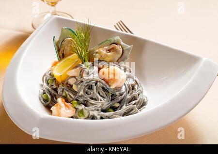 Des fruits de mer l'encre de seiche noire coulored pâtes spaghetti cuisine italienne typique. Banque D'Images