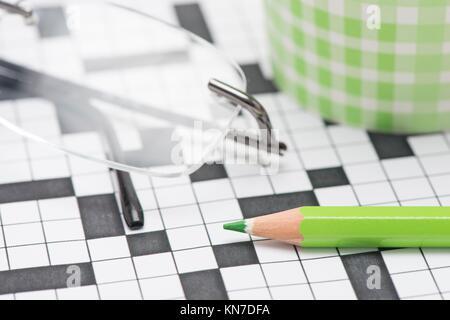 Libre de mots croisés et de crayon vert. Image conceptuelle de la résolution de problèmes, trouver des solutions Banque D'Images
