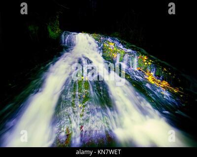 Peinture lumière nuit en cascade. Cascade blanche sur ruisseau de montagne. L'eau mousseuse floue sur la roche moussue. Banque D'Images