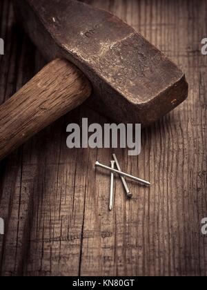 Vintage hammer and nails couché sur la surface en bois de Workbench. Image conceptuelle d'amélioration à la maison, Banque D'Images