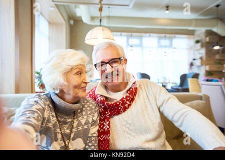 Portrait of happy senior couple holding camera et prendre photo sur selfies assis dans Noël cafe Banque D'Images