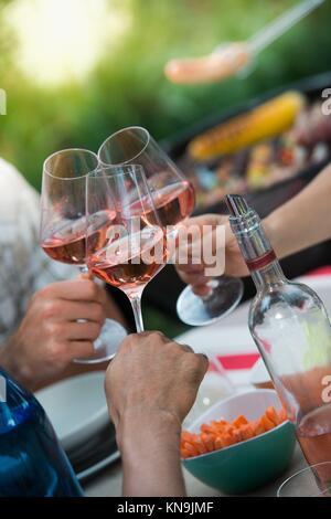 Gros plan d'amis Tossing verres de vin rouge dans une partie. Banque D'Images