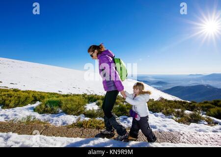 Scène d'hiver famille heureuse mère de tenir la main de trois ans enfant randonnées ensemble dans la neige sur la Banque D'Images