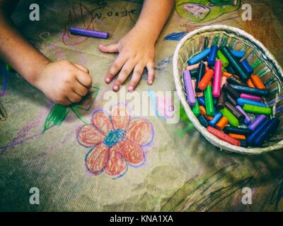 Dessin de l'enfant avec un panier de crayons de cire sur craft papier d'emballage. High angle view.