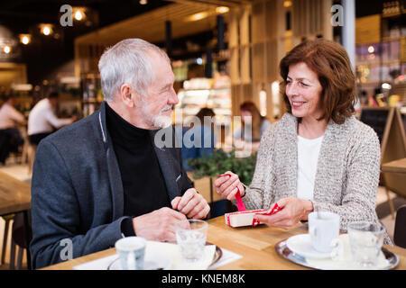 Couple avec un présent dans un café. Le temps de Noël. Banque D'Images