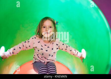 Fille dans le tube sur l'escalade à la caméra en souriant Banque D'Images
