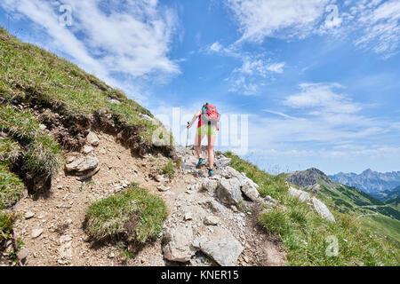 Vue arrière du female hiker randonnées jusqu'Tannheim mountains, Tyrol, Autriche Banque D'Images