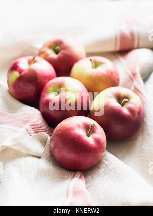 6 pommes rouges sur lin tissu cuisine, close-up