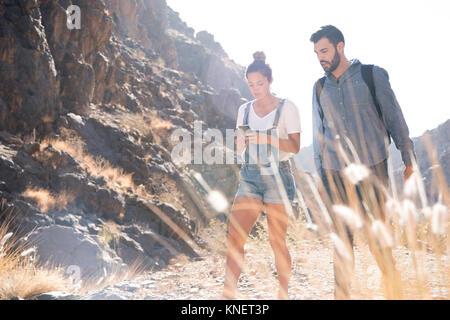 Les jeunes randonnées couple looking at smartphone pendant la randonnée dans la vallée, Las Palmas, Canaries, Espagne Banque D'Images