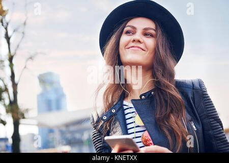 Portrait de jeune femme au chapeau trilby en ville Banque D'Images