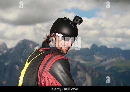Cavalier de base portant sur l'appareil photo d'action avec wingsuit casque, Dolomites, Canazei, Trentin-Haut-Adige, Banque D'Images