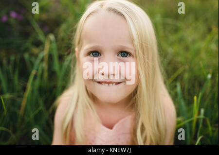 Portrait of blond haired girl looking at camera smiling Banque D'Images