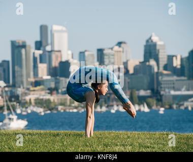 Adolescente en plein air, en équilibre sur les mains en position de yoga Banque D'Images