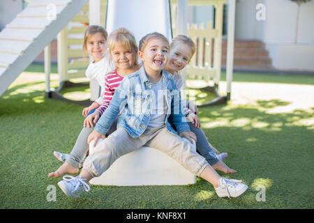 Filles et garçons à l'âge préscolaire, portrait assis sur l'aire de glisse dans le jardin Banque D'Images