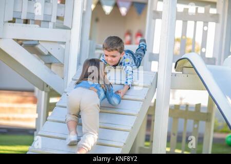 Fille et garçon à l'âge préscolaire, coup de main à ramper jusqu'à la rampe d'escalade dans la région de jardin Banque D'Images