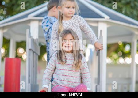 Filles et garçons à l'âge préscolaire, portrait en haut de l'aire de glisse dans le jardin Banque D'Images