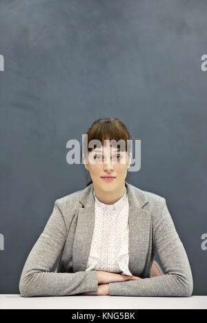 Portrait d'un fier et déterminé young businesswoman sitting avec un fond gris et de l'espace pour copier Banque D'Images