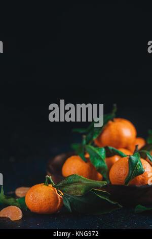 Agrumes sur une plaque de bois avec des feuilles vertes. Tangerines dynamique sur un fond sombre. La photographie Banque D'Images
