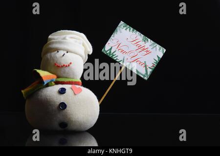 """Le Snowman figure la tenue d'étiquette avec stick et ci-joint le texte """"Bonne Année!"""" écrit dessus, entouré de Banque D'Images"""