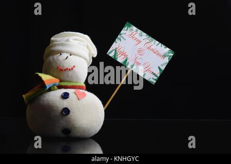 """La figure bonhomme holding a placard. Texte """"Joyeux Noël et Bonne Année!"""" écrit dessus, et entouré de branches Banque D'Images"""