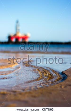 L'eau coule dans l'océan. C'est marée basse. Le soleil du soir s'allume la scène. Dans l'arrière-plan un flou hors Banque D'Images