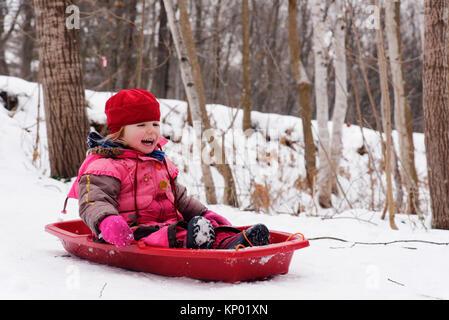 Un rire petite fille (3 ans) de la luge au Québec Banque D'Images