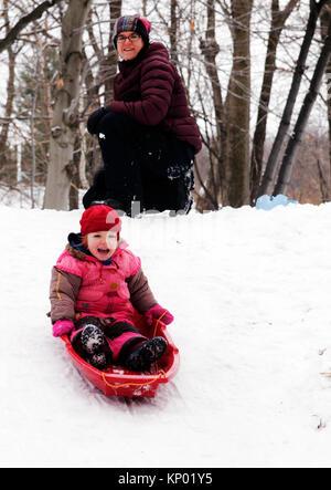 Une petite fille (3 ans) de la luge au Québec, tandis que la maman regarde sur Banque D'Images