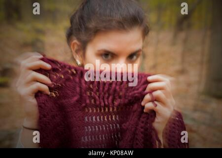 Jeune femme dans les bois tenant un châle, couvrant partiellement son visage. Banque D'Images
