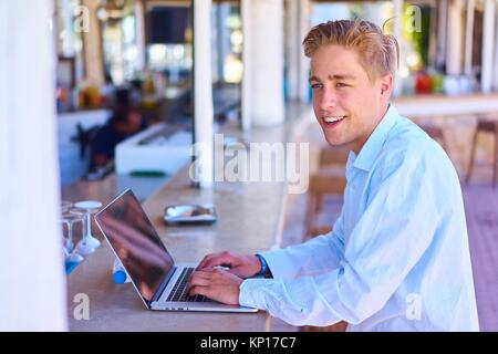 Man with laptop computer sitting at bar Banque D'Images