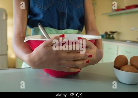 Close-up of hands of woman holding bowl dans la cuisine à la maison Banque D'Images