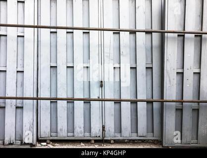 Vieille porte en bois qui bloque sur le rail métallique de l'ancien entrepôt. Banque D'Images