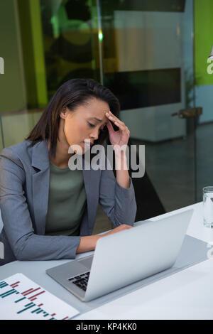 Tendu businesswoman using laptop at desk in office Banque D'Images