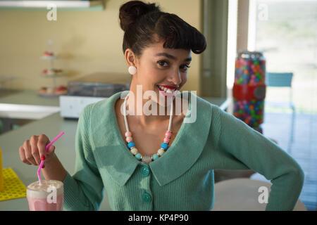 Portrait of smiling woman holding paille à la caméra en at restaurant Banque D'Images