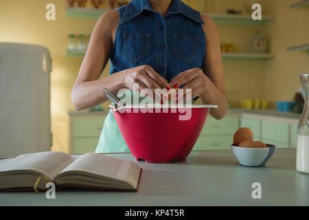 Jeune femme casser un oeuf dans un bol à mélange de cuisine Banque D'Images