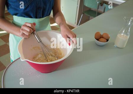 Jeune femme en fouettant le mélange dans le bol dans la cuisine à la maison Banque D'Images