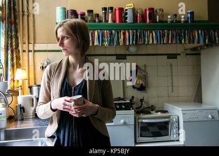 Tilburg, Pays-Bas. Hot woman boire une tasse de thé pendant que appuyé contre un lavabo de cuisine vintage. Banque D'Images