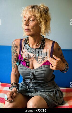 Tilburg, Pays-Bas. Adulte mature woman with tattoo's, portrait, alors qu'il était assis sur un sofa du salon.
