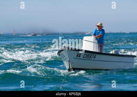 Caucasian homme plus âgé avec son chapeau, la conduite d'un petit bateau de pêcheur dans l'océan en Bretagne, France. Il est dans la fin des années 60.