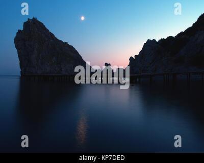 Pleine lune sur la mer Noire: d'énormes rochers se reflètent sur la surface de l'eau, voie de la lune, en Crimée. Banque D'Images