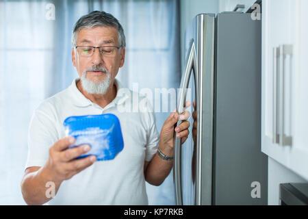 Est-ce toujours bien? Man dans sa cuisine par le réfrigérateur, à la date de péremption d'un produit qu'elle a Banque D'Images